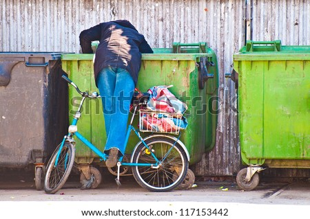 Poor woman searching in garbage