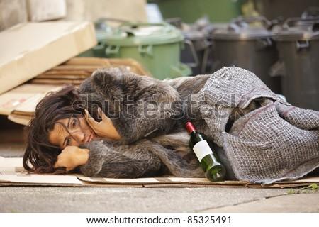poor woman tramp lying among bin with wine bottle - stock photo