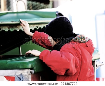 poor young boy tries to eat into the waste box in winter  - stock photo