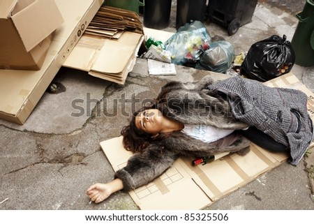 poor young drunk woman lying in trash in city street - stock photo