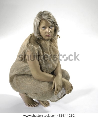 poor young girl dressed in a gunnysack while cowering on the ground. Studio shot in light back - stock photo