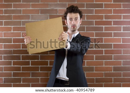 poor young unshaved businessman standing pleading with a blank sign - stock photo