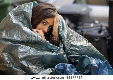 poor young woman wrapped in plastic tarpaulin - stock photo