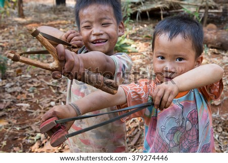 POP PRA, TAK, THAILAND - FEB 20, 2016 : Unidentified Akha ethnic boys are holding sling shot with rubber bands to shoot the ball clay on FEBRUARY 20, 2016 at KM48, Pop Pra, Tak, Thailand. - stock photo