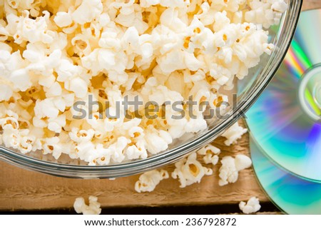 Popcorn And A Movie - This is a shot of a bowl of popcorn next to a DVD.  - stock photo
