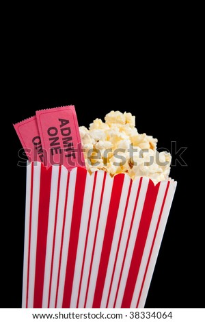 Popcorn and movie tickets on a black background - stock photo