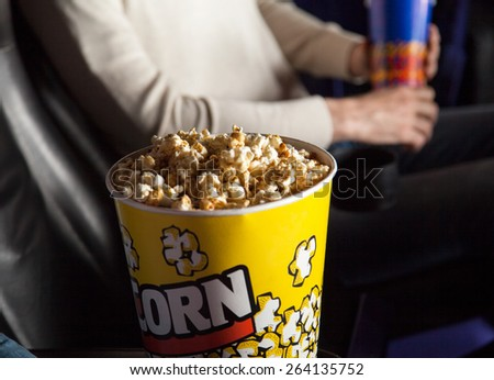 Popcorn bucket at cinema theater with man sitting in background - stock photo