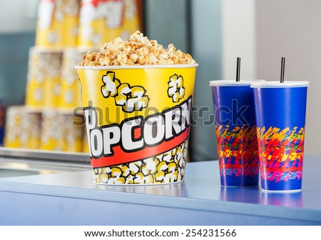 Popcorn bucket with cold drinks on concession counter at cinema - stock photo