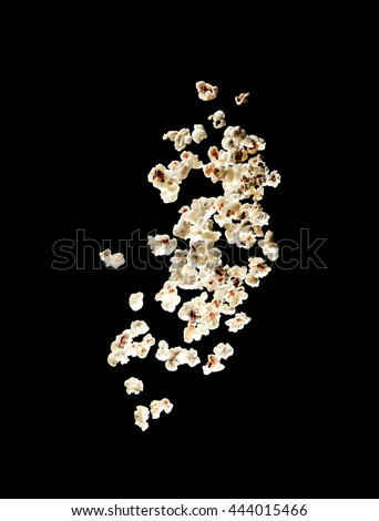 popcorn bursting in the air over black background