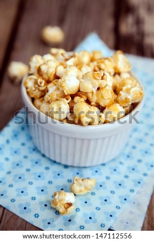 Popcorn covered with caramel in white bowl on wooden table  - stock photo