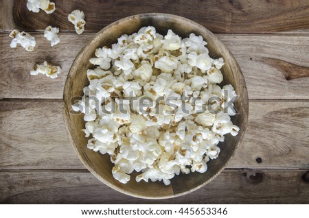 Popcorn in a bowl on wooden surface