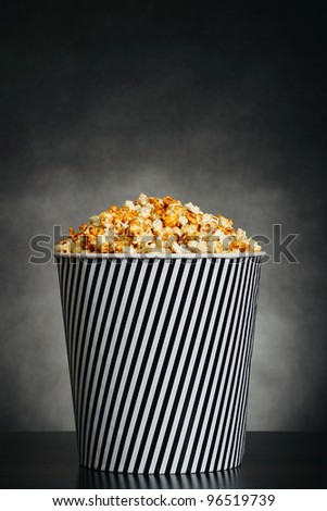 Popcorn in a container on black background - stock photo
