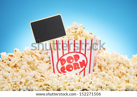 Popcorn in box overflowing with freshly popped corn against a blue background - stock photo