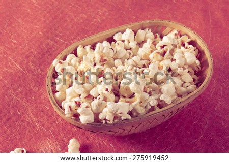 popcorn in bucket over red cloth - retro style - stock photo