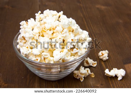 Popcorn in glass bowl on wooden table - stock photo