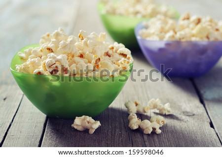 Popcorn in plastic bowls over wooden background - stock photo