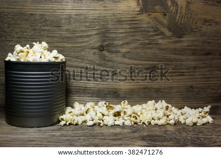 Popcorn in tin on wooden background. Space for text. - stock photo