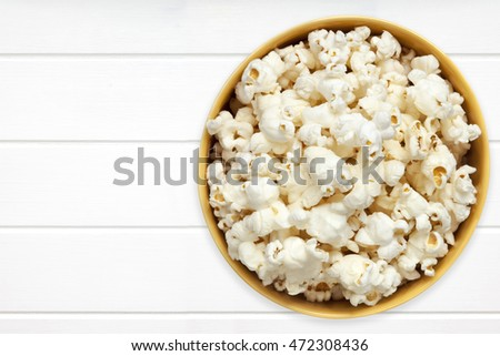 Popcorn in yellow bowl over white timber.  Top view.