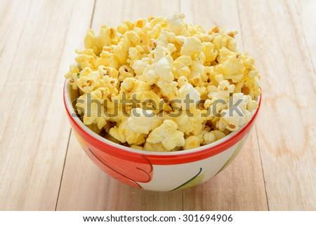 popcorn on wooden table. - stock photo
