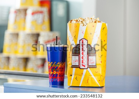 Popcorn paperbag and cold drink on concession counter at cinema - stock photo
