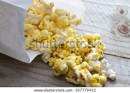 Popcorn spilling from plain white bag onto picnic table - stock photo
