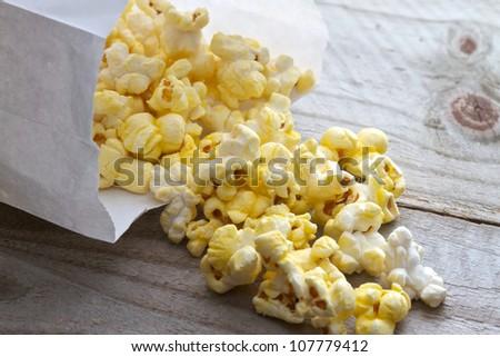 Popcorn spilling from plain white bag onto picnic table - stock photo