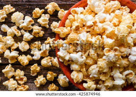 popcorn with caramel on a wooden background close up - stock photo