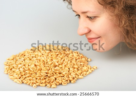 Popped wheat grains and beautiful girl - stock photo