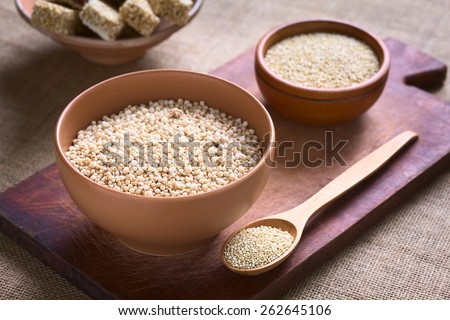 Popped white quinoa (lat. Chenopodium quinoa) cereal in bowl with raw quinoa seeds in the back photographed with natural light (Selective Focus, Focus one third into the quinoa cereal) - stock photo