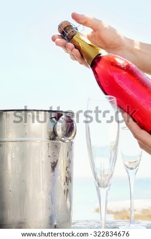 Popping champagne for a special occasion party at the beach, summer time outdoor lifestyle  - stock photo