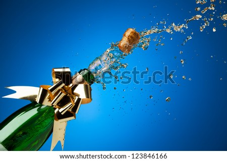 Popping cork from Champaign bottle with gold bow on it and splashes all around the blue background - stock photo