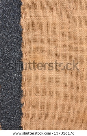 Poppy lying on sackcloth space for text - stock photo