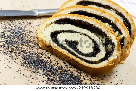 Poppy seed Roll on a wooden surface, closeup. - stock photo