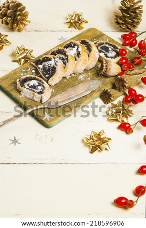 poppy seed rolls with an old dessert knife on aged wooden table