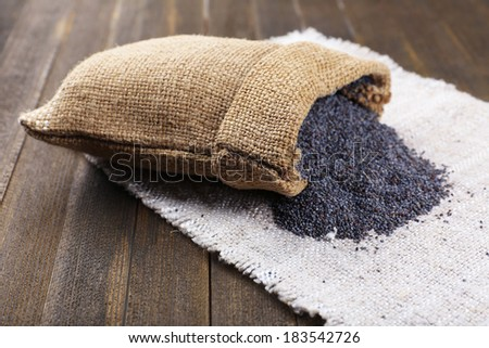 Poppy seeds in sack on table close-up - stock photo