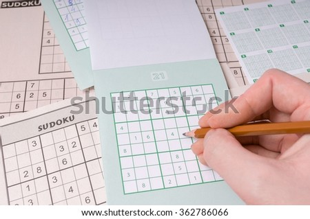 Popular brain teaser logic game sudoku. Hand is writing numbers in grid. - stock photo