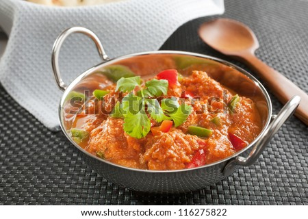 Popular Indian curry Chicken Jalfrezi, chicken stir fried with spices, with a tomato sauce and red and green capsicums, in a balti dish. - stock photo