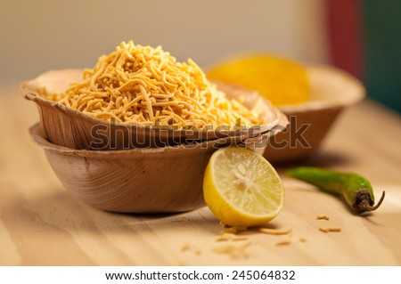 Popular street side indian snacks - Fried Sev with lime and chili - stock photo