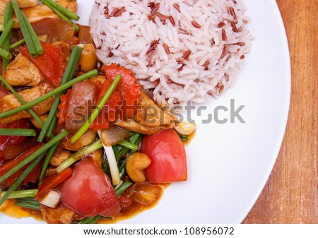 Popular thai and chinese dish: stir-fried chicken with cashew nut. Served with red and white rice. Delicious! - stock photo