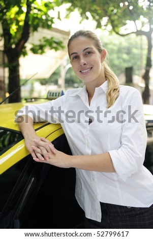 porait of a proud female taxi driver with her new cab - stock photo