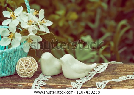 Porcelain birds against the background of a green grass. Nearby a sky-blue wicker basket with the blossoming apple-tree branch.