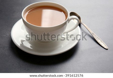 Porcelain cup of tea with milk on gray background - stock photo