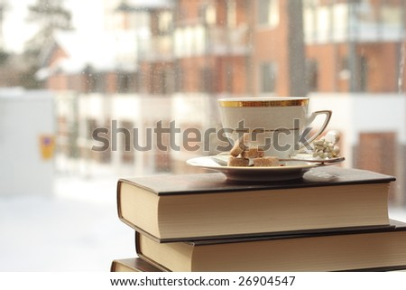 Porcelain cup with coffee on a stack of books by the window