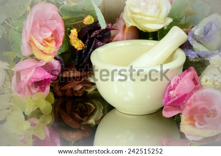 Porcelain herbal medicine grinder on floral background. - stock photo