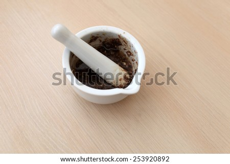 Porcelain mortar with sauce on a wooden table - stock photo