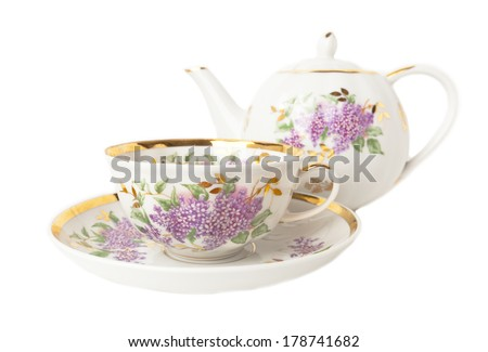Porcelain teapot, teacup and saucer with floral ornament isolated over white
