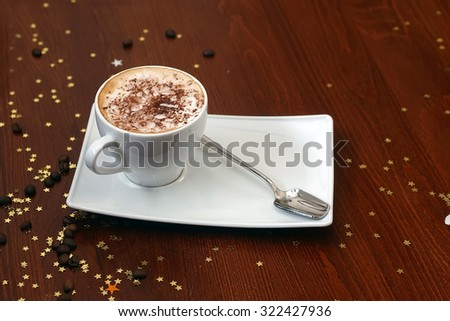 Porcelain white cup of cappuccino with froth with grated chocolate and teaspoon on rectangular saucer on table with gold stars and coffee beans, horizontal photo                              - stock photo