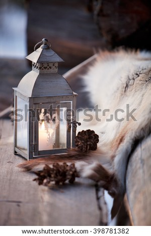 Porch decoration with lantern and reindeer fur - stock photo