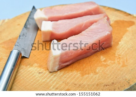 Pork and knife on wooden./Pork and knife.