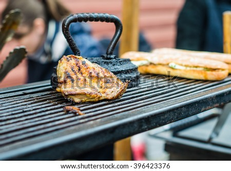 Pork and sandwiches from baguette fried on the grill grate . The cook prepares a meal at an outdoor market . Close-up on the coals . - stock photo